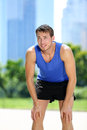 Tired man runner exhausted after sport exercise male jogger catching breath sweating run workout in summer with urban Stock Photography