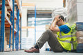 Tired man sitting on the couch with a headache in warehouse Royalty Free Stock Image