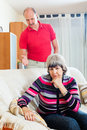 Tired mature woman listening to angry husband family quarrel women at home Stock Images