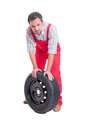 Tired mechanic resting on car wheel Royalty Free Stock Photo