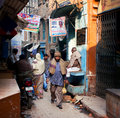 Tired people returning home after working through the narrow streets varanasi india citizens of old town in varanasi approximately Stock Image