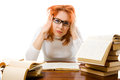 Tired red-haired girl in glasses with books. Royalty Free Stock Photography