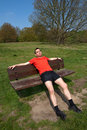 Tired Runner Resting on Sunny Park Bench Royalty Free Stock Photo