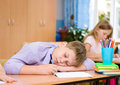 Tired schoolboy at a lesson at school Royalty Free Stock Photo