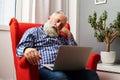 Tired senior man sleeping with laptop Royalty Free Stock Photo