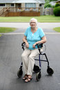 Tired senior woman sitting on walker in the driveway Stock Photo