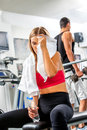 Tired slim woman with towel on bench in gym relax Stock Photography