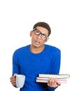 Tired student closeup portrait young man wearing glasses holding books and coffee cup preparing for finals exam test isolated on Royalty Free Stock Photography