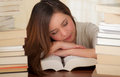 Tired student completely sleep over the books in the library Royalty Free Stock Photo