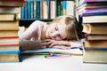 Tired student girl with books sleeping on the table. education, session, exams and school concept . Royalty Free Stock Photo