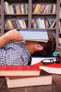 Tired student side view of young man covering his face with book while lying on the hardwood floor with other books laying all Royalty Free Stock Photos