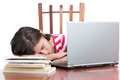 Tired student sleeping on her desk with a laptop computer and books isolated white Royalty Free Stock Photos
