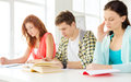 Tired students with textbooks and books at school Royalty Free Stock Photo