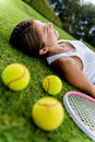 Tired tennis player lying on the floor outdoors Stock Photo