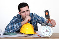 Tired tradesman about to smash his alarm clock Stock Photography