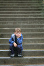 Tired of waiting a cute little boy sitting on some big concrete steps bored and shallow depth field copy space Stock Photos