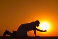 Tired and weaken man on all fours prays for help reached his hand to gold sunset sun disk to pray Royalty Free Stock Photos
