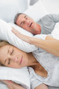 Tired wife blocking her ears from noise of husband snoring in bedroom at home Stock Images