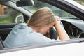 Tired woman asleep on steering wheel in her car Stock Images