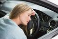 Tired woman asleep on steering wheel in her car Stock Photo