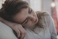 Tired woman falling asleep on the couch Royalty Free Stock Photo