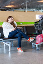 Tired woman looking at tablet pc in airport lounge with luggage hand cart Royalty Free Stock Images