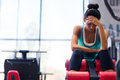 Tired woman sitting on exercises machine sports in fitness gym Royalty Free Stock Image