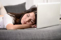Tired woman sleeping on the laptop keyboard fallen asleep over Stock Image