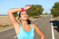 Tired woman sweating after running runner hard in countryside road exhausted sweaty marathon training on hot summer hispanic Royalty Free Stock Images