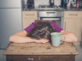 Tired woman with tea in kitchen Royalty Free Stock Photo
