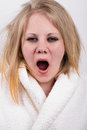Tired yawning young woman with messy hair wearing a white robe with a white background bankom Royalty Free Stock Photo