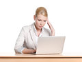 Tired young businesswoman sitting at a desk with laptop Stock Photo