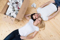 Tired young couple lying head to head on the floor in their new house Stock Images