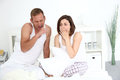 Tired young couple yawning in bed sitting their sleepwear on top of the bedclothes Royalty Free Stock Images
