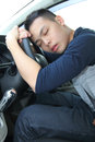 Tired young man asleep at the wheel a falling steering Stock Photography