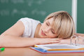 Tired young student sleeping on her books with head resting arms and a sweet expression as she relaxes in the classroom Stock Photography