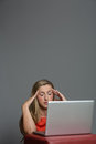 Tired young woman working on a laptop very with an headache and massaging head with closed eyes Stock Images