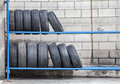 Tires storage of in a row some for cars are exhibited in an blue iron shelf Royalty Free Stock Images