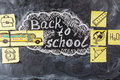 Title Back to school written by chalk on the black chalkboard and the school bus drawn on the pieces of paper