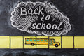 Title Back to school written by chalk on the chalkboard and the school bus drawn on pieces of paper