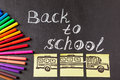 Title Back to school written by chalk and image of the school bus drawn on the pieces of paper on the chalkboard