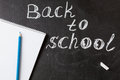 Title Back to school written by white chalk and the the notebook with blue pencil  on the black school chalkboard Royalty Free Stock Photo