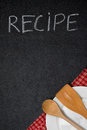 Title recipe written in chalk on a blackboard empty plate and spoon the corner vertical Royalty Free Stock Photos
