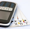 Téléphone portable sur 3 cartes de jeu utilisées Photographie stock libre de droits