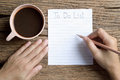 To do list woman hand write on wooden table with coffee cup Royalty Free Stock Photography