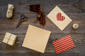 To wrap gift. Box, kraft paper, envelope, greeting card, ribbon, sciccors on wooden background top view