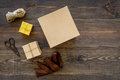 To wrap gift. Boxes, kraft paper, ribbon, sciccors on wooden background top view copyspace
