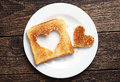 Toast bread with cut out heart shape slice of on vintage wooden background Royalty Free Stock Image