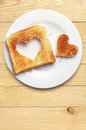 Toast bread with cut out heart shape slice of on wooden table Stock Image