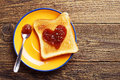 Toast bread with jam in shape of hearts on vintage wooden table top view Stock Photo